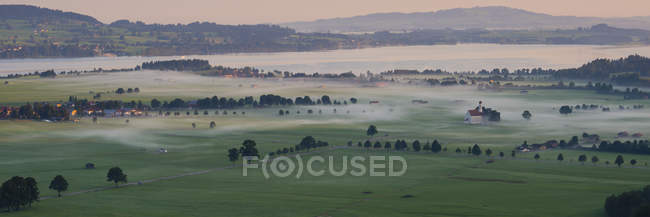 Alemania, Baviera, Schwangau, pintoresco lago Forggensee y Iglesia de St Coloman - foto de stock