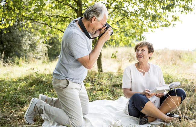 Senior man photographing woman sitting on blanket outdoors — Stock Photo
