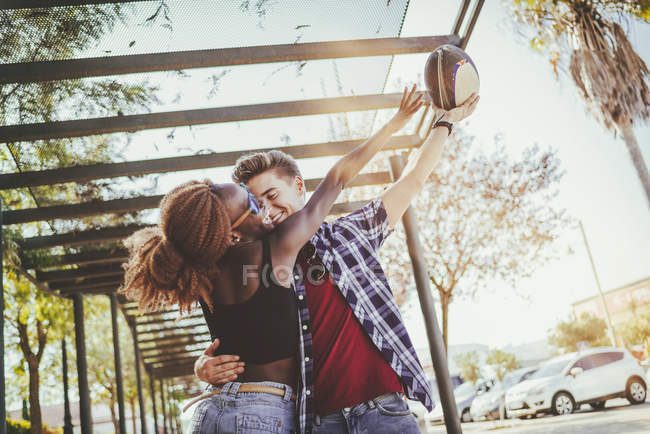 Happy young couple playing with rugby ball — Stock Photo