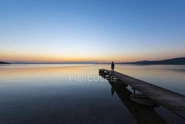 Italy, Umbria, Lake Trasimeno, silhouette of man standing on jetty watching sunset — Stock Photo