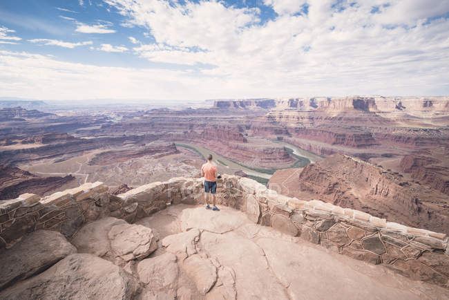 USA, Utah, Young man standing on Dead Horse Point looking to Colorado River — Stock Photo