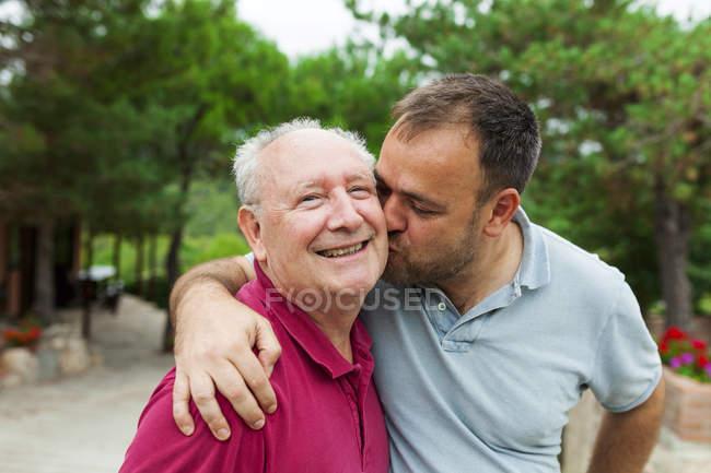 Дорослий сина, поцілунки і обійми старий батько на відкритому повітрі — стокове фото
