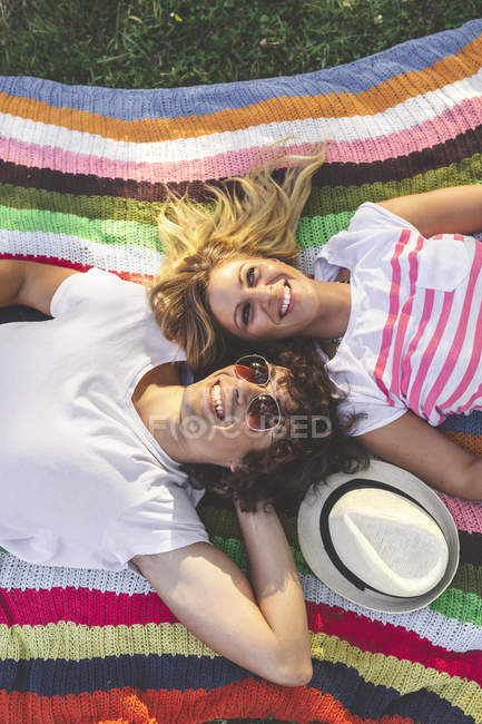 Happy young couple lying on blanket in park — Stock Photo