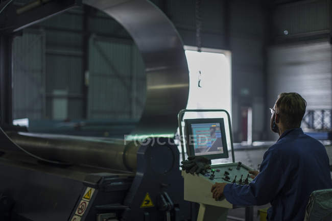 Worker operating machinery at control panel in steel factory — Stock Photo