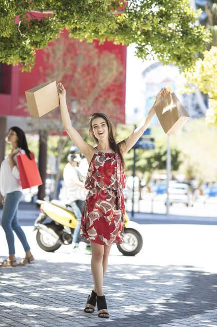 Счастливая женщина на торговой улице с сумками — стоковое фото