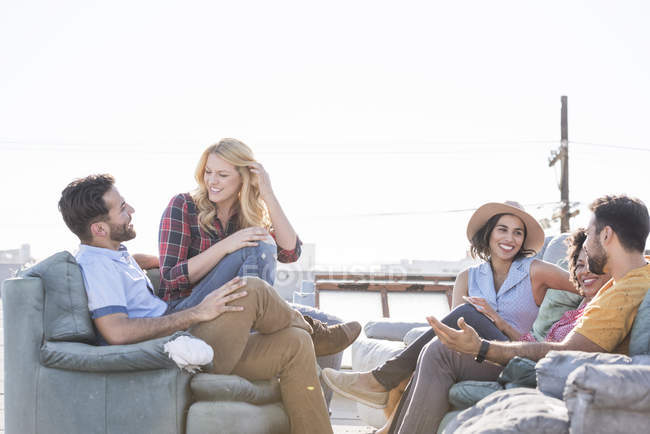 Friends at rooftop party in bright sunshine — Stock Photo