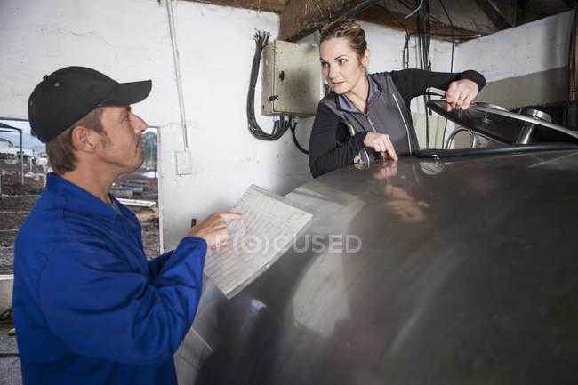 Man and woman at dairy tank at work — Stock Photo