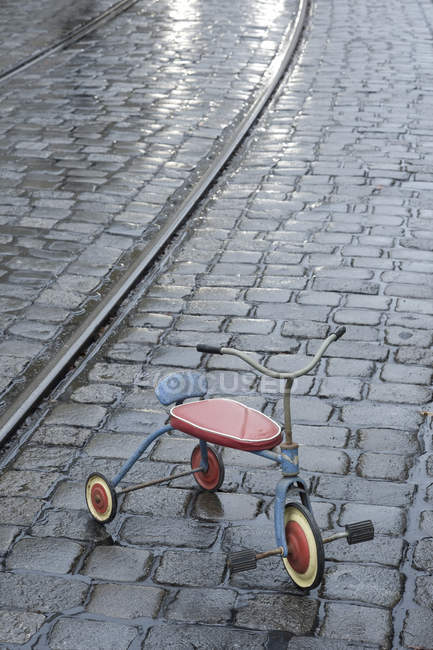 Old children's tricycle on rainy pavement — Stock Photo