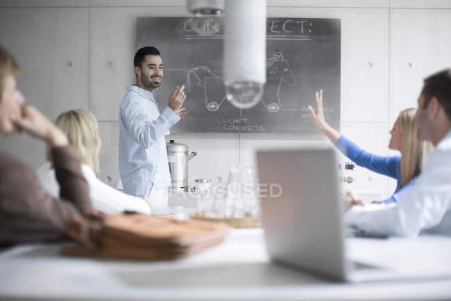 Jóvenes que trabajan juntos en la oficina moderna - foto de stock