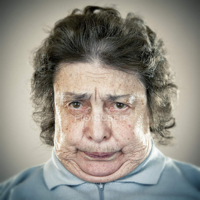 Portrait of senior woman pulling face and looking at camera — Stock Photo