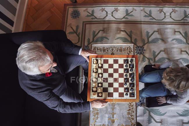 Вид сверху на дедушку и внука, играющих в шахматы в гостиной — стоковое фото