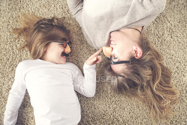 Mother and little daughter lying on the carpet having fun with comedy glasses — Stock Photo