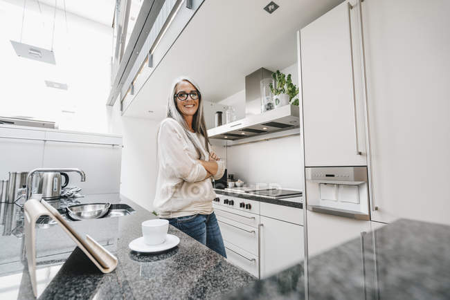 Smiling woman with long grey hair in kitchen — Stock Photo