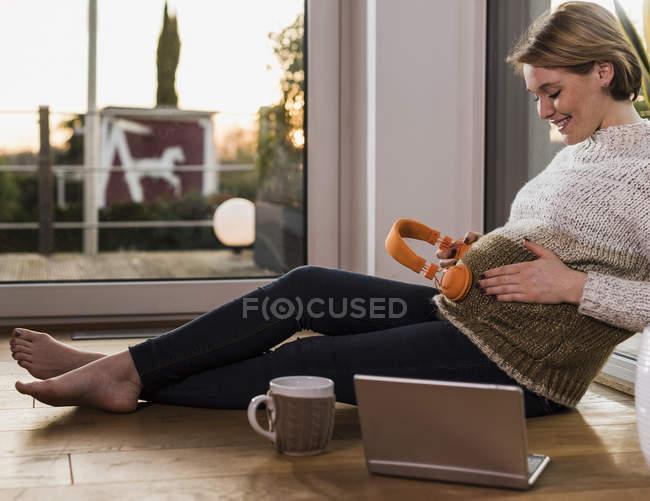 Беременная женщина сидит на полу и держит наушники к животу — стоковое фото