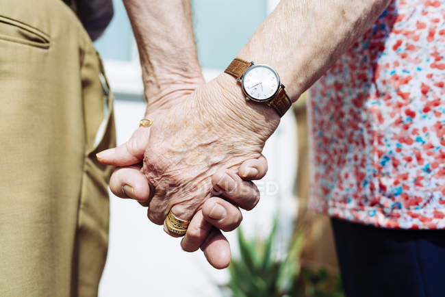Back view of senior couple holding hands, close-up — Stock Photo