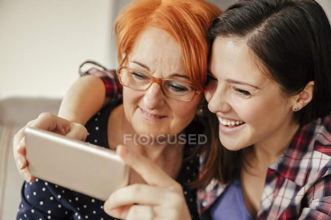 Mère et fille adulte prenant selfie sur le téléphone intelligent assis sur le canapé — Photo de stock