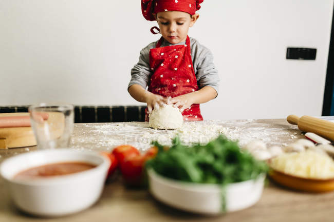 Petit garçon préparant des pizzas à la maison. Habillé comme un chef — Photo de stock