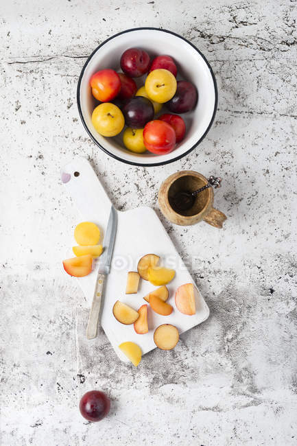 Various plums in bowl, chopping board with knife — Stock Photo