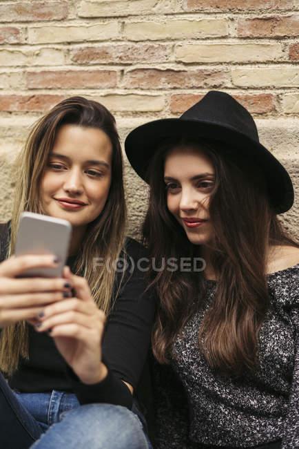 Deux meilleurs amis utilisant un smartphone devant un mur de briques — Photo de stock