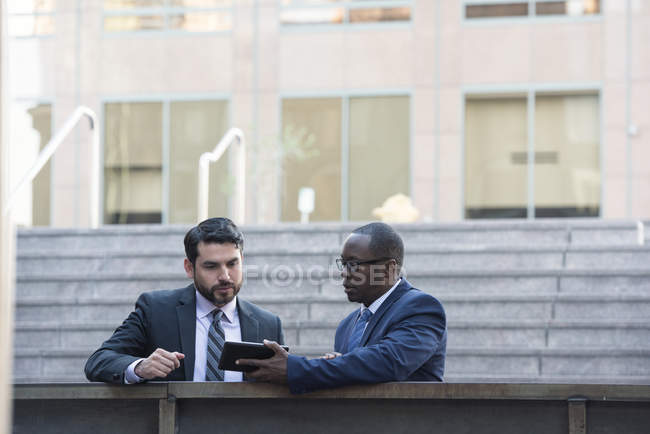 Two confident businessmen sharing tablet outdoors — Stock Photo