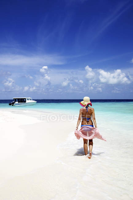 Maldives, woman walking on sandy beach — Stock Photo