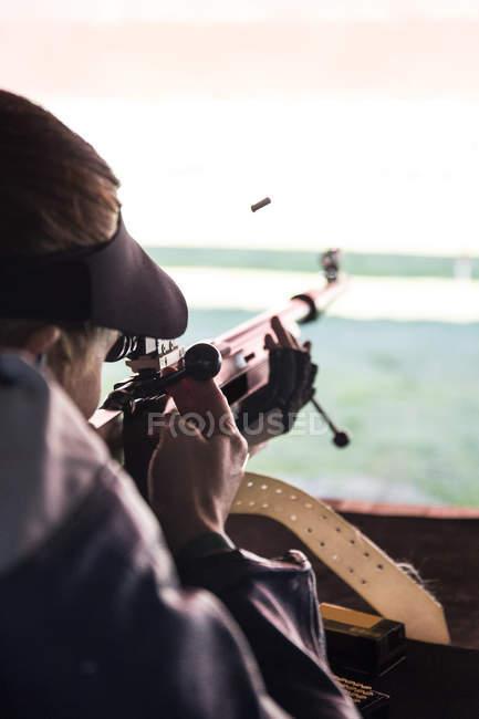 Bala no ar e mulher atirando rifle esportivo em um campo de tiro — Fotografia de Stock