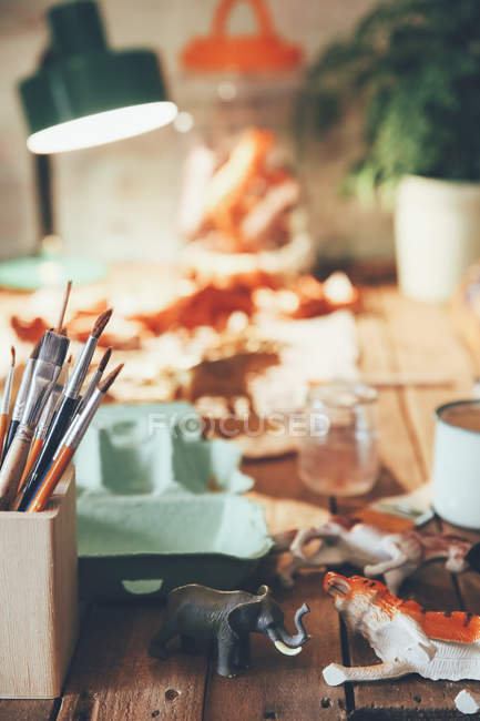 Table with pot of paintbrushes, plastic animals, lamp and plant in the background — Stock Photo