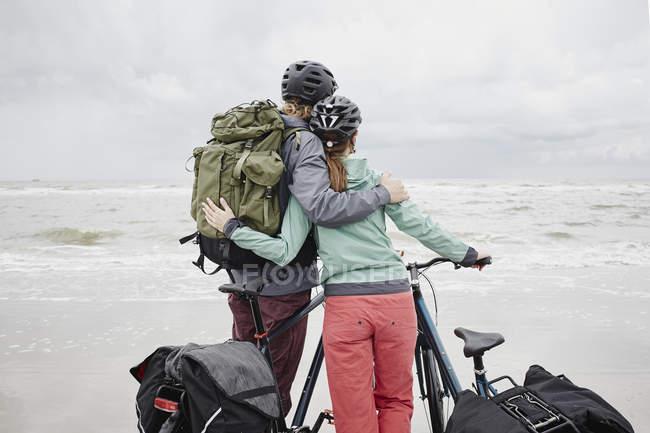 Pareja con las bicicletas en la playa - foto de stock