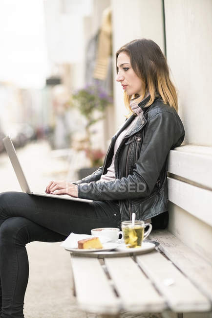 Young woman sitting on outdoor bench using laptop — Stock Photo