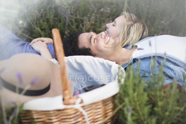 Coppia giovane sdraiata nel campo di lavanda con cestino — Foto stock