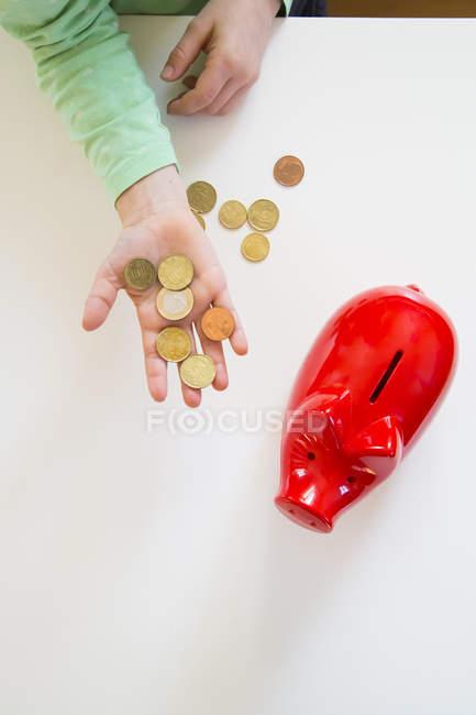 Mädchens Hand mit Münzen und ein rotes Sparschwein — Stockfoto