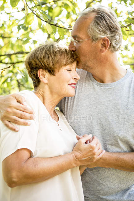 Senior couple cuddling outdoors in green garden — Stock Photo