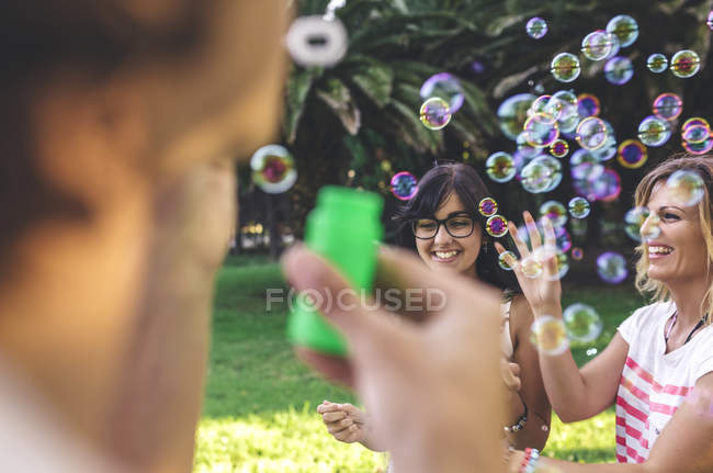 Young happy friends having fun and playing with soap bubbles in park — Stock Photo