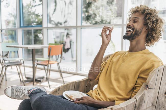 Смеющийся молодой человек ест сэндвич — стоковое фото