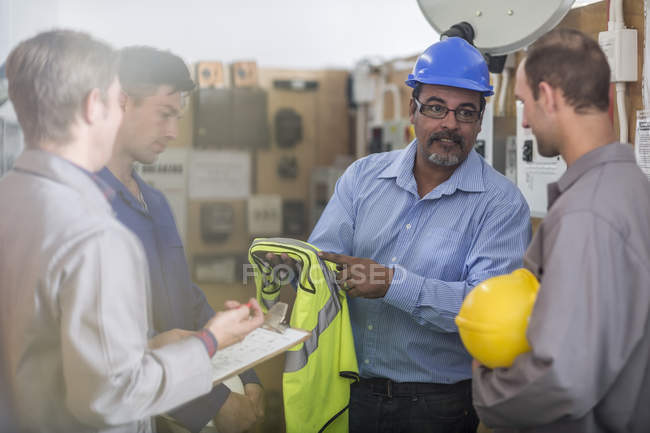 Instructor in a workshop showing safety vest — Stock Photo