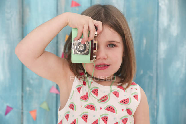 Portrait of little girl playing with vintage toy camera — Stock Photo
