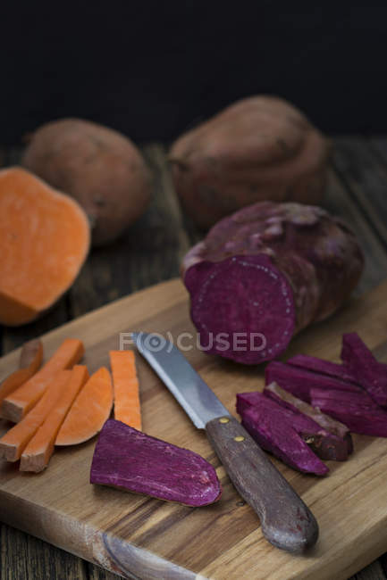 Closeup view of sliced orange and purple potatoes on wooden cutting board — Stock Photo