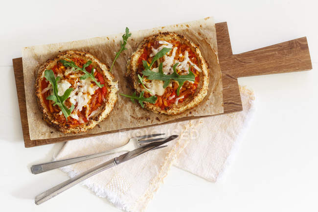 Two homemade glutenfree mini pizzas with cauliflower, pumpkin and rocket on wooden board — Stock Photo