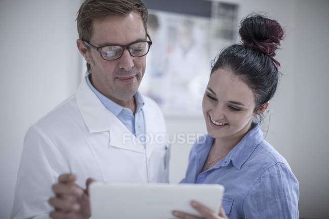 Man in lab coat and woman looking at tablet — Stock Photo