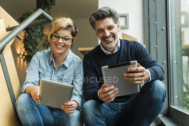 Businessman and businesswoman sitting on stairs and using digital tablets — Stock Photo