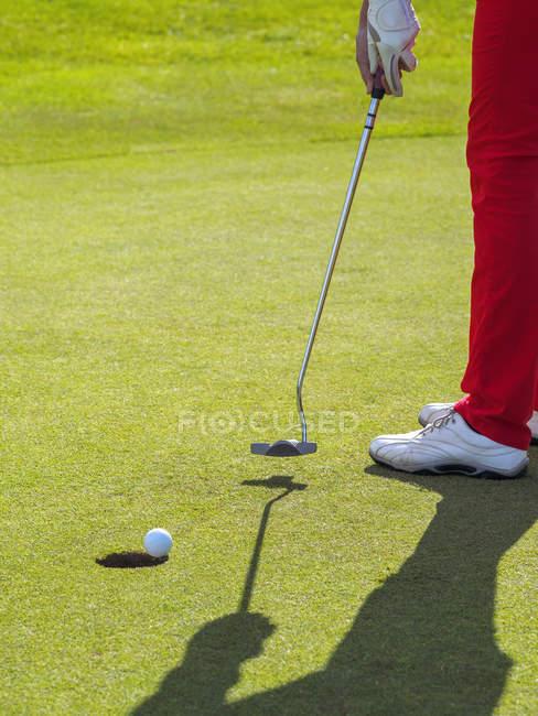 Golfer auf Golfplatz schlägt Ball in Loch, Nahaufnahme, Teilsicht — Stockfoto