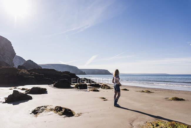 Adolescente en la playa con rocas - foto de stock
