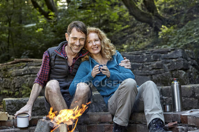 Happy couple sitting at camp fire — Stock Photo