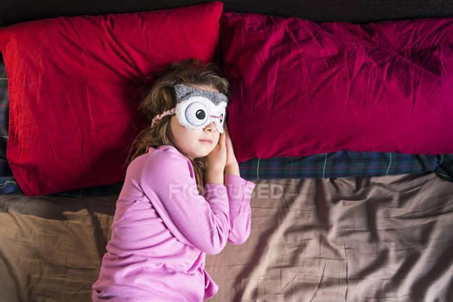 Girl with sleep mask lying on bed — Stock Photo