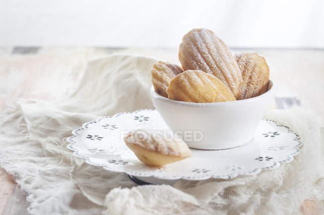 Крупным планом вид Madeleines с пудрой сахара в белых блюда и ткани — стоковое фото
