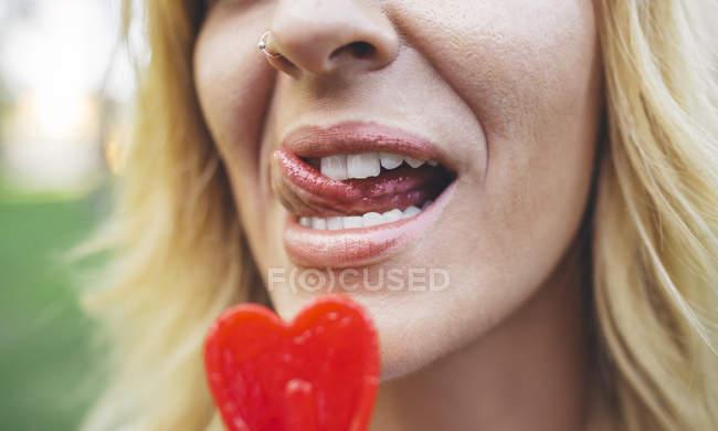 Primo piano di giovane donna leccare lecca lecca-lecca a forma di cuore — Foto stock