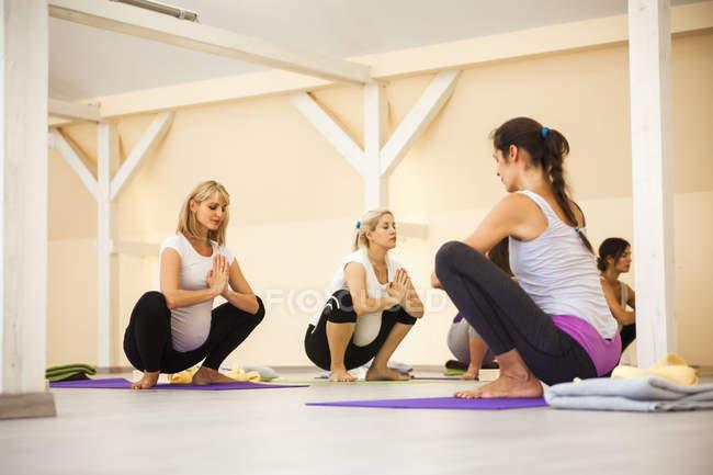 Женщины делают упражнения на уроке пренатальной йоги — стоковое фото