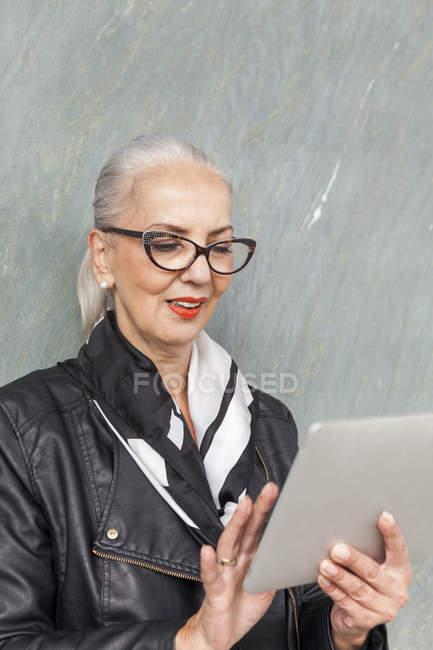 Porträt einer modischen reifen Frau mit Tablette — Stockfoto