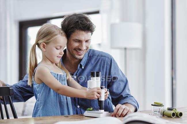 Батько і дочка вивчення з Бінокулярний вдома — стокове фото