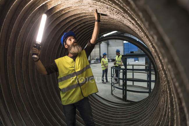 Worker examining giant construction tube — Stock Photo